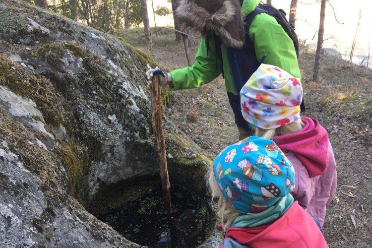 Barnen mäter djupet på en av Gålös jättegrytor