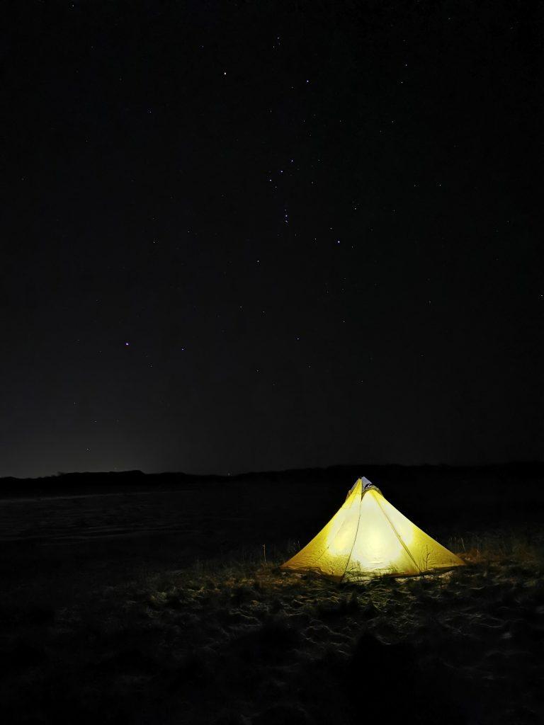 På himlen ovanför tältet syns stjärnor