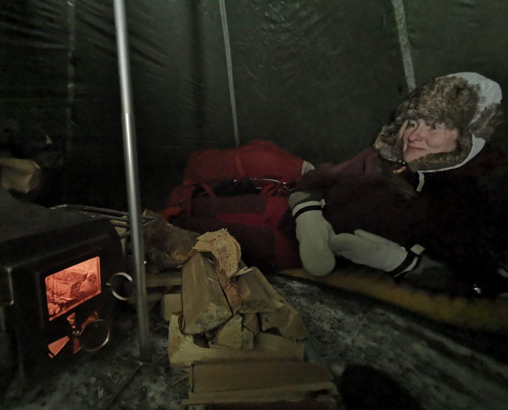 Jag kurar i tältet och njuter av kaminens värme som börjar sprida sig