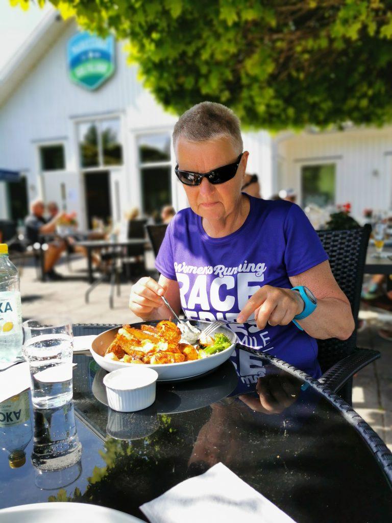Gunnel njuter av gott kycklingspett på Mariestad Golfklubb